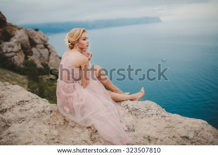 Beautiful bride posing on the coast with angelic dress. Bride in wedding dress stands on a cliff with a beautiful sea view from the top. Beautiful bride by the sea - stock photo
