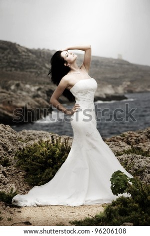 Beautiful bride posing on the coast with angelic lighting - stock photo