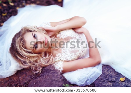 Beautiful bride posing outdoor. Wedding dress, curly blond hair. - stock photo