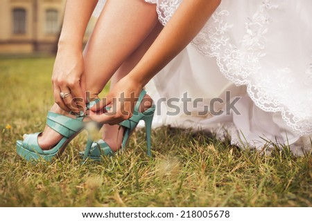 Beautiful bride preparing to get married in white dress and fasten her tiffany blue shoes on the grass in the park alone. outdoors. copy space - stock photo