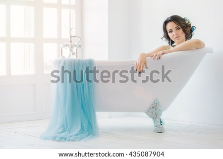 Beautiful bride relaxing in the tub. Wedding dress colors serenity white Studio. With makeup and hair. - stock photo