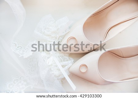 Beautiful bride's wedding shoes, garter and wedding rings - stock photo