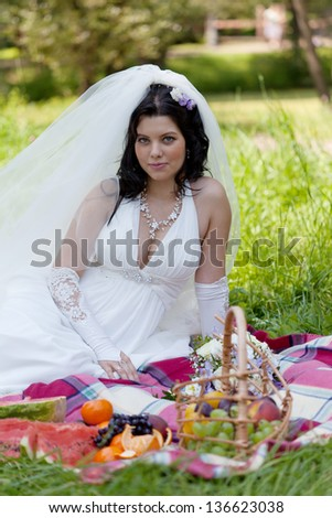 beautiful bride sits on a grass with a big basket with fruit - stock photo