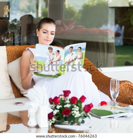 Beautiful bride sitting and reading magazine about golf - stock photo