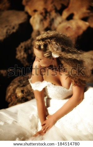 Beautiful bride sitting on a rocky beach in a windy day. Romantic moment. - stock photo