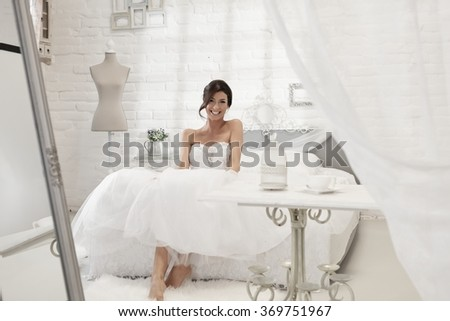 Beautiful bride sitting on bed in white bedroom, smiling happy.