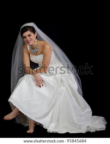 Beautiful bride sitting relaxed set against a black background with bare feet leaning forward smiling.
