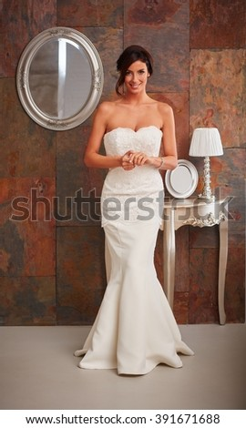 Beautiful bride standing in wedding gown, smiling happy. Full size. - stock photo