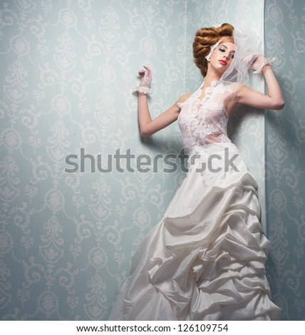 Beautiful bride standing indoors with white dress - stock photo