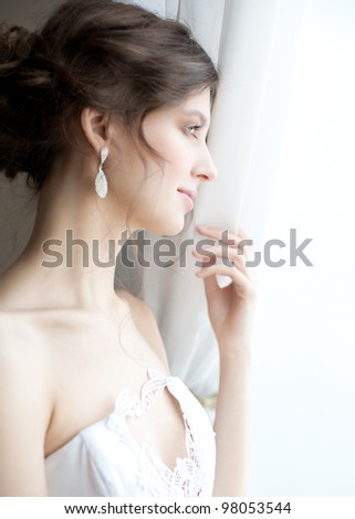 Beautiful bride standing near the window and looking away - stock photo