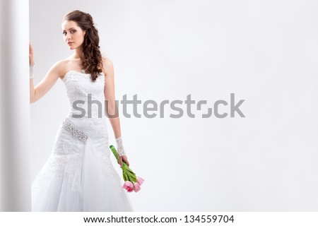 beautiful bride standing near white column, horizontal studio shot - stock photo