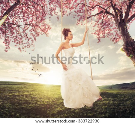 Beautiful Bride swing in the spring meadow - stock photo