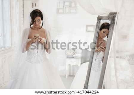 Beautiful bride using mobilephone in white bedroom. - stock photo