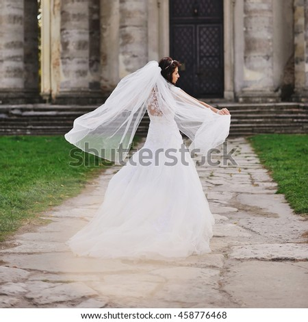 beautiful bride walking next to old church