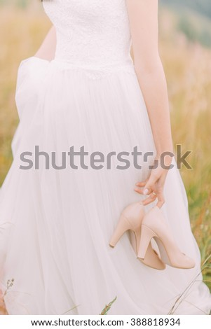 Beautiful bride walks with heels on hands. Green field close up  - stock photo