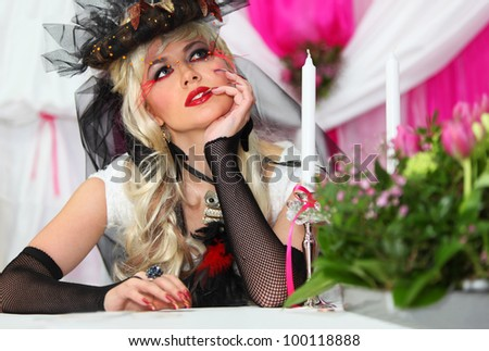 beautiful bride wearing black net gloves and unusual hat sits at table with candles and dreams
