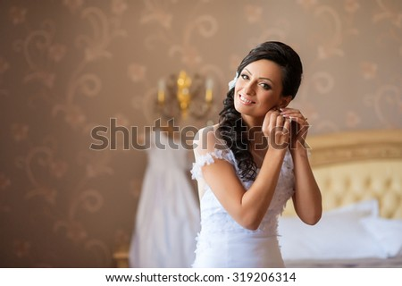 beautiful bride wears an earring in the mirror - stock photo