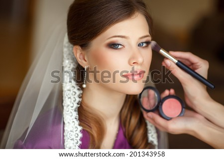 Beautiful bride wedding makeup and hairstyle. Stylist makes makeup bride on wedding day. portrait of young bride at wedding day. series. soft tonality - stock photo