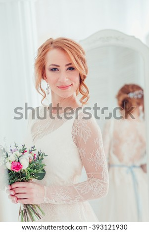 Beautiful Bride Wedding Portrait Indoors, newlywed woman in wedding dress with bridal flowers. Happy Bride posing in hotel room