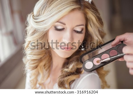 Beautiful bride wedding with makeup and curly hairstyle. Stylist makes make-up bride on wedding day. Beauty portrait of young woman at morning. - stock photo