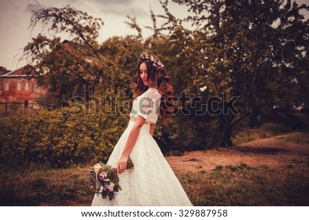 beautiful bride with a bouquet of flowers walking in the park in Europe - stock photo