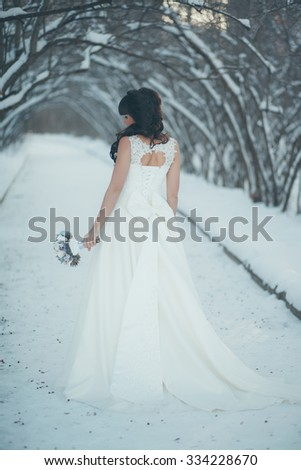 Beautiful bride with a bouquet standing in a snowy winter park at the beautiful snow-covered trees - stock photo