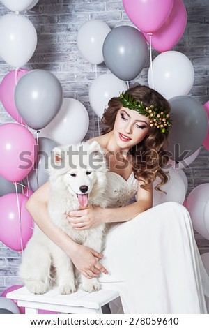 Beautiful bride with a Samoyed dog - stock photo