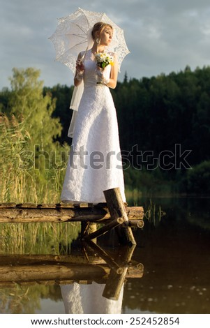 Beautiful bride with an umbrella on a bridge near the water in the forest - stock photo