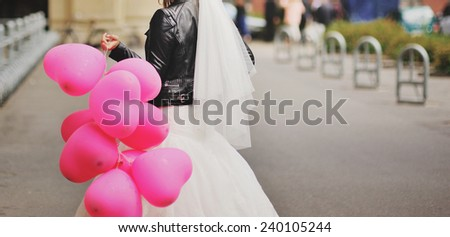 Beautiful bride with balloons downtown.  - stock photo