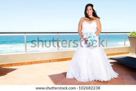 beautiful bride with bouquet and sea view - stock photo