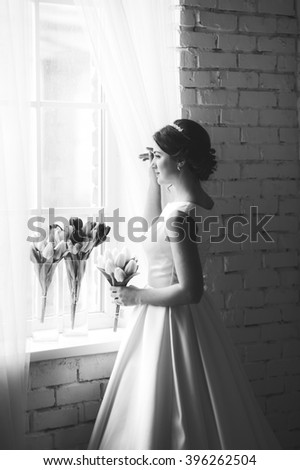 Beautiful bride with bouquet before wedding ceremony near window