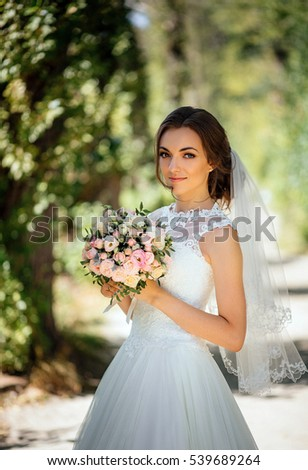 Beautiful bride with bouquet in park