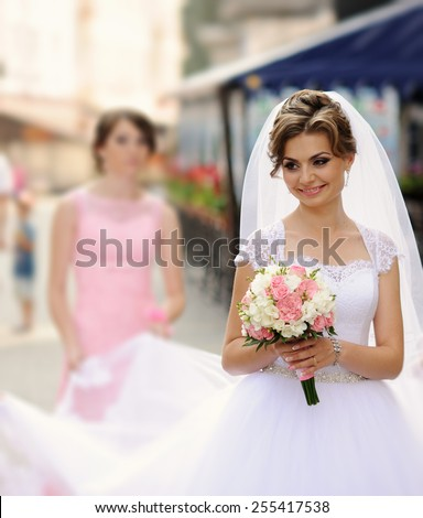 Beautiful bride with bouquet of flowers outdoor - stock photo