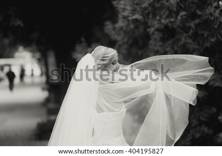 Beautiful bride with bouquet of flowers outdoor