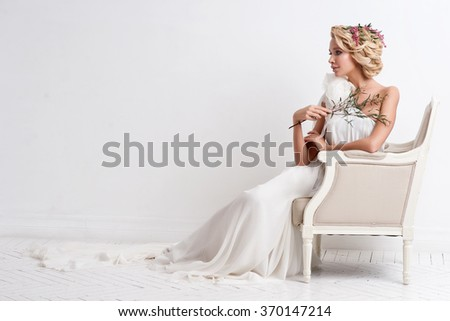 Beautiful bride with bouquet over white background - stock photo