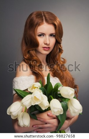 beautiful bride with curly red hair in wedding dress with flowers - stock photo