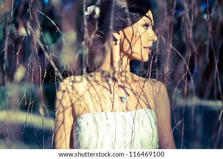 Beautiful Bride with diamonds posing in nature - stock photo