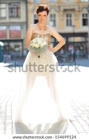 Beautiful bride with elegant gold/white wedding dress - stock photo