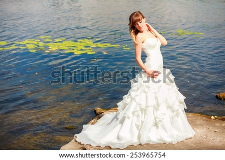 Beautiful bride with elegant white wedding dress with hand to head