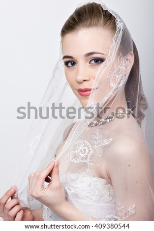 Beautiful bride with fashion wedding hairstyle. Close-up portrait of young gorgeous bride. Wedding. girl covers her face with a veil - stock photo