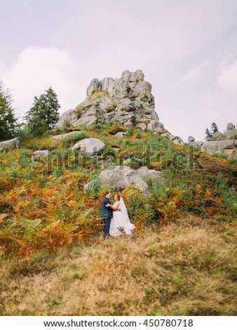 Beautiful bride with handsome groom embracing on background of rocky Carpathian mountains.