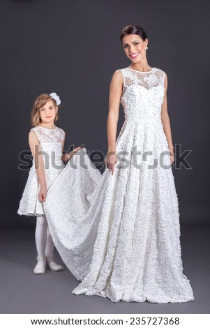 Beautiful bride with her pretty little bridesmaid in studio - stock photo