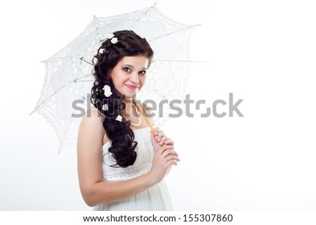 beautiful bride with long hair in wedding dress standing and holding an open umbrella.  Isolated on white background. Wedding style. Fashion model woman in bridal dress with umbrella