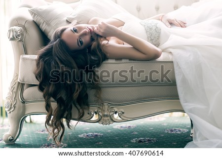 Beautiful bride with long hanging curly hair lying on the sofa in a wedding dress in a luxury room. Portrait of relaxing woman. - stock photo