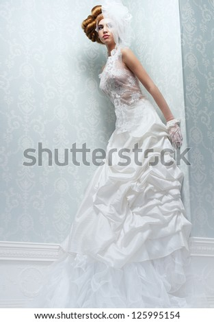 Beautiful bride with long white wedding dress and veil - stock photo