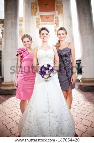 Beautiful bride with two bridesmaids against colonnade - stock photo