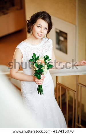 Beautiful bride with wedding bouquet of goes up the stairs, indoors. - stock photo