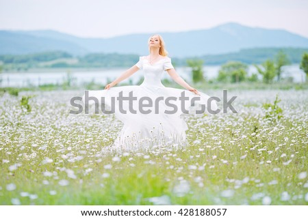beautiful bride with white hair in a field of daisies