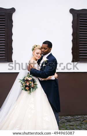 Beautiful bride woman in long white lace dress veil and elegant groom african American man just married couple hug outdoors on wedding day