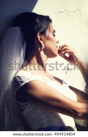 Beautiful bride woman with eyes closed in white wedding dress and veil dreams on sunny day over old wall